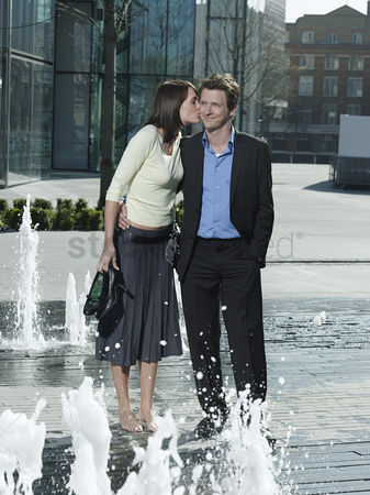 Pocket : Mid-adult couple standing between water jets of fountain woman kissing man