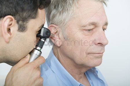 Examination : Mid adult doctor checks hearing of senior patient