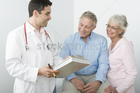 Mid adult man : Mid adult doctor explains test results to senior couple