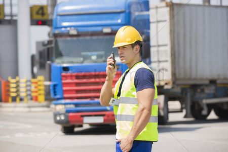 Truck : Mid adult man using walkie-talkie in shipping yard