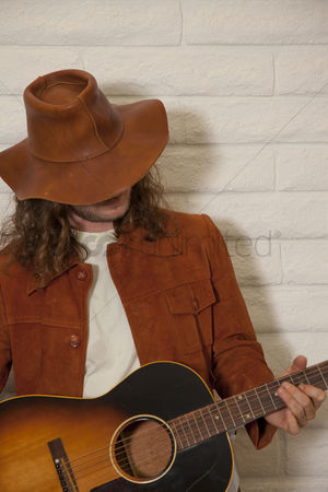 fd844cf5d5465 1917249 Cowboy hat   Mid adult man wearing cowboy hat and playing guitar