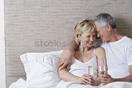 Celebration : Middle-aged couple drinking champagne in bed