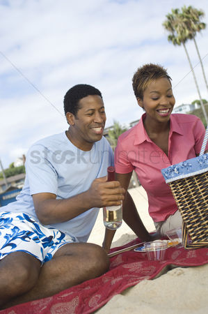 Wine bottle : Middle-aged couple having picnic on beach