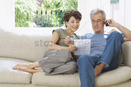 Couples : Middle-aged couple paying bill by phone