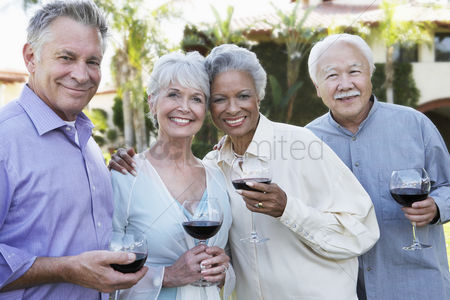 Husband : Middle-aged friends standing outside drinking wine from wineglasses