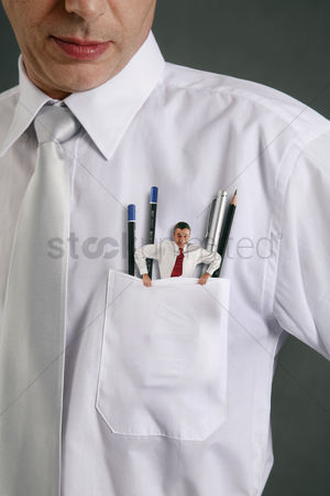 Pocket : Mini sized businessman trying to get out from businessman s pocket
