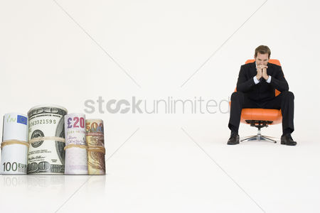 British ethnicity : Money rolls with pensive businessman on chair representing financial problems