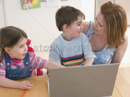 Offspring : Mother and children at table with laptop