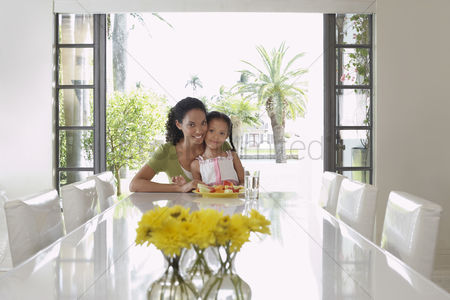 Sitting on lap : Mother and daughter  5-6 years  sitting at dining table