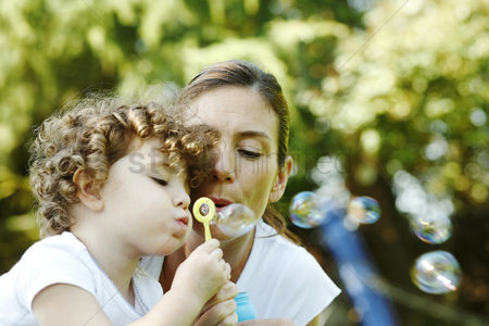 Blowing : Mother and daughter blowing out soap bubbles together