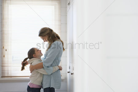 Ponytail : Mother and daughter embracing standing in front of window