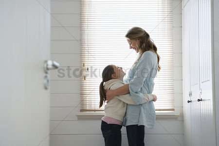 Interior background : Mother and daughter hugging standing in front of  window