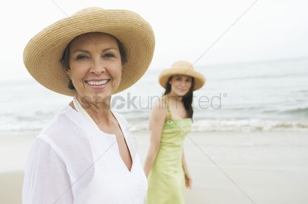 Daughter : Mother and daughter in sunhats on beach