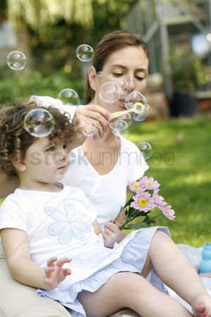 Blowing : Mother and daughter playing with soap bubbles in the park