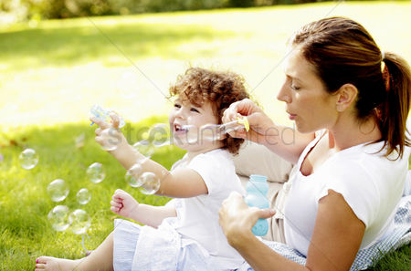 Cheerful : Mother and daughter playing with soap bubbles