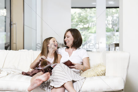 Appearance : Mother and daughter reading book in living room portrait