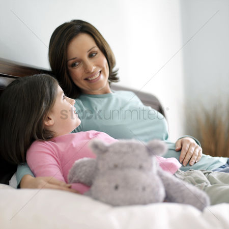 Rest : Mother and daughter resting on the bed talking