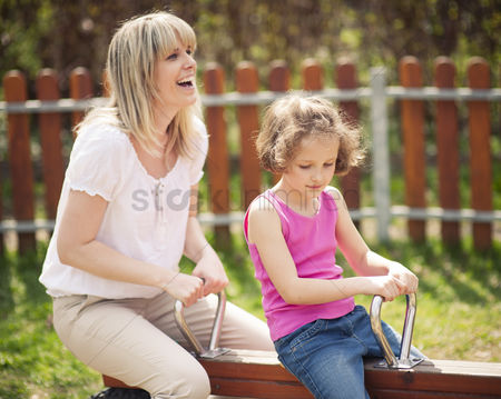 Spring : Mother and daughter ride seesaw together
