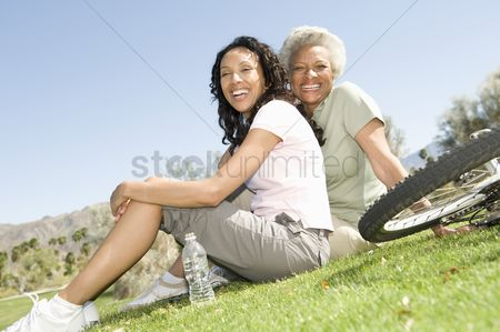 Senior women : Mother and daughter sit in park with mountain bikes