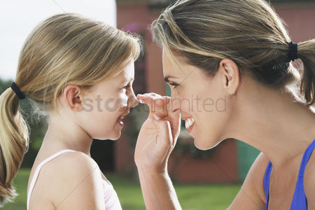 Ponytail : Mother applying sunscreen on daughter s  5-6  nose smiling side view profile