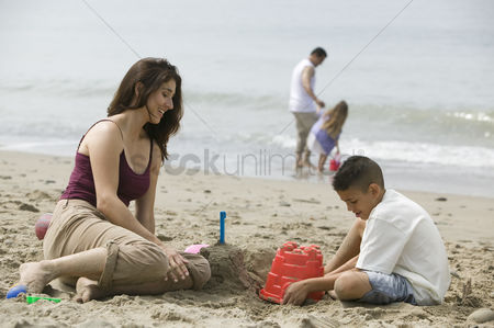 Pre teen : Mother building sandcastles with son on beach