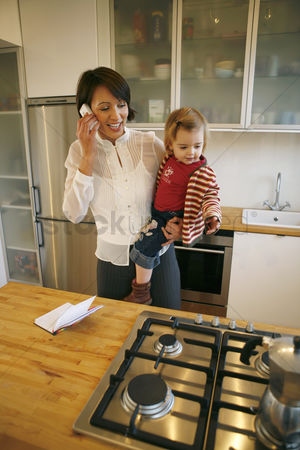 Cellular phone : Mother carrying daughter while talking on the phone