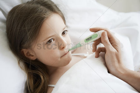 Thermometer : Mother checking temperature of daughter in bed close up of daughter
