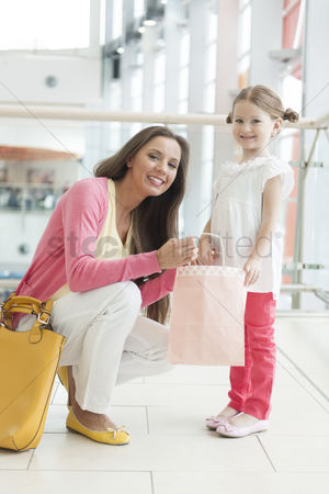 Offspring : Mother giving daughter paper shopping bag