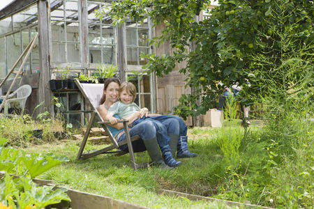 Greenhouse : Mother sitting with son in garden portrait