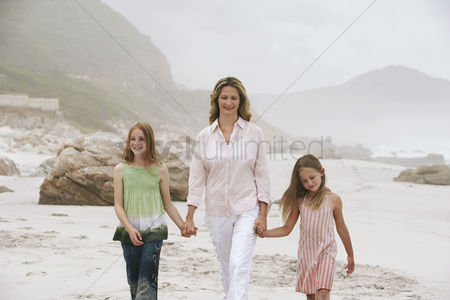 40 44 years : Mother with two daughters  7-9 10-12  walking on beach