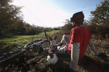 Transportation : Mountain biker and dog sitting beside bike in countryside