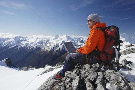 Winter : Mountain climber using laptop on mountain peak