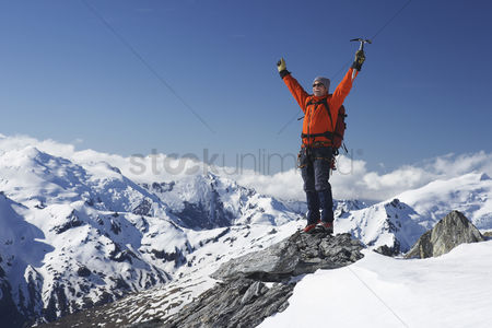 Winter : Mountain climber with arms raised on top of mountain peak