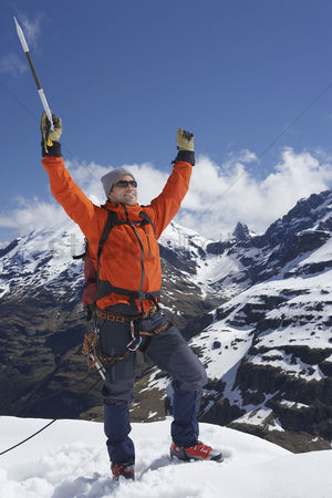 Arm raised : Mountain climber with arms raised on top of snowy peak