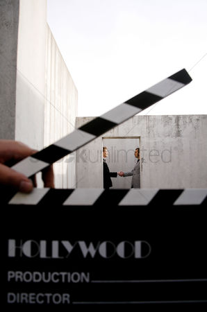 Client : Movie director holding clapboard with businessmen shaking hands in the background