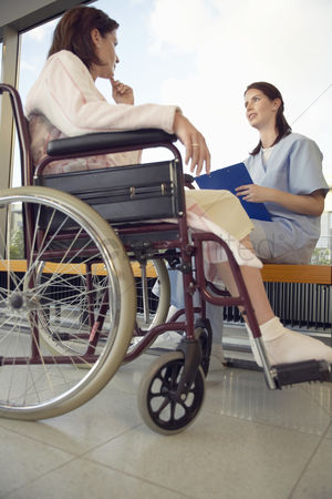 Relationships : Nurse talking to patient in wheelchair low angle view