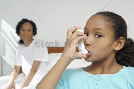 Medication : Nurse watching girl  7-9  using inhaler in hospital