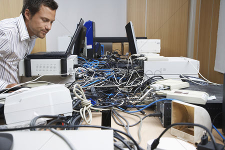 Frowning : Office worker looking at mess of wires connecting computers and printer in office