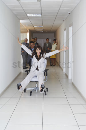 Pushing : Office workers playing on office chairs in hallway