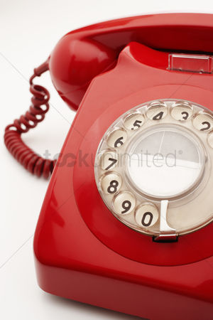 Vintage : Old fashioned red telephone in studio cropped