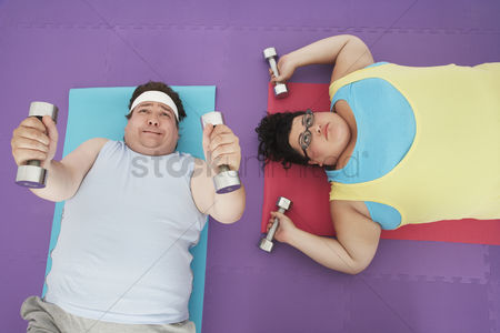 Dumbbell : Overweight man and woman lying down lifting dumbbells overhead view