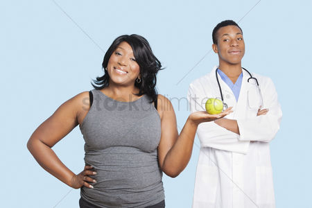 Blue background : Overweight mixed race woman holding green apple with doctor over blue background