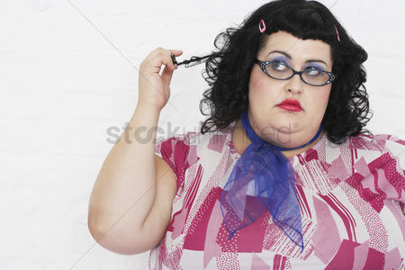 Pink : Overweight woman twisting strand of hair portrait