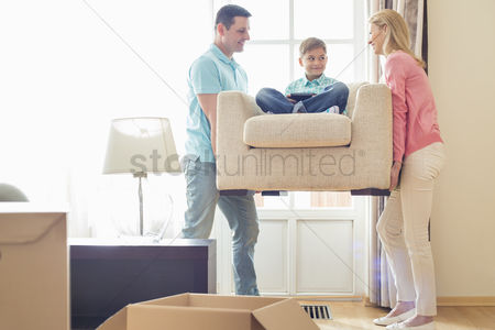 Three quarter length : Parents carrying son on armchair in new house