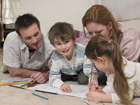Young boy : Parents on floor coloring with children
