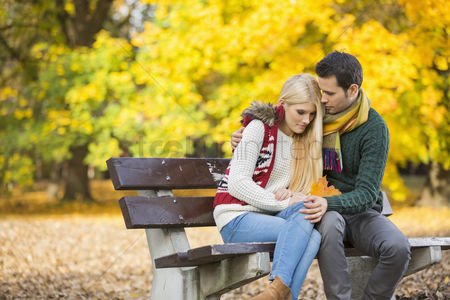 Shyness : Passionate young man hugging shy woman on park bench during autumn