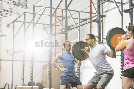 Muscle training : People assisting man in lifting barbell at crossfit gym