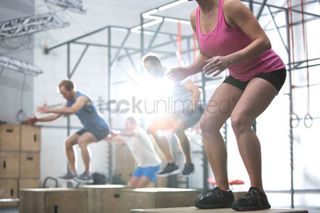 Women : People doing box jump exercise in crossfit gym