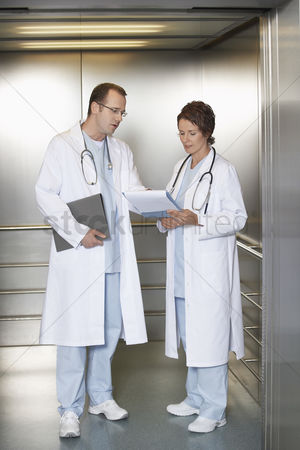 Advice : Physicians discussing chart in hospital elevator