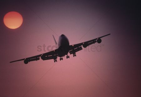Transportation : Plane flying below setting sun at sunset